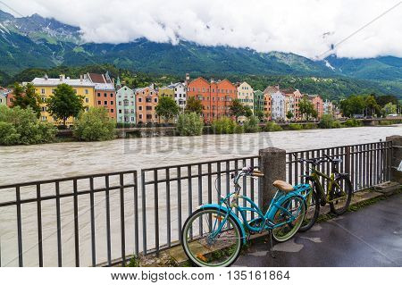 INNSBRUCK AUSTRIA - 18TH JUNE 2016: Colourful buildings along the side of the River Inn in Innsbruck during the day. Bikes and railings can be seen.