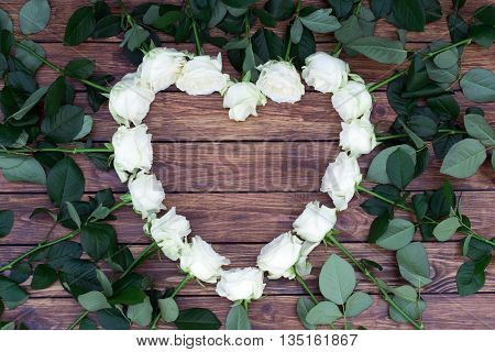 Heart of roses with green leaves on a background of brown wooden planks with a place for an inscription