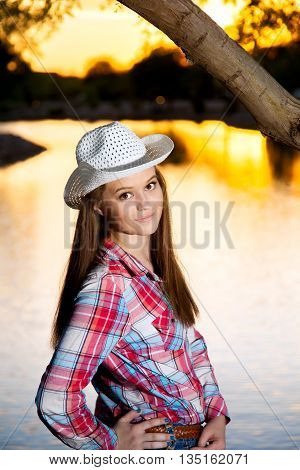 A teenage cowgirl looks over her shoulder at the camera as she poses for a portrait in front of a lake at sunset.