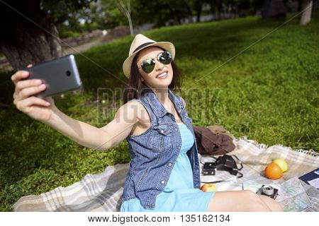 Happy female tourist is making selfie on the mobile phone. She is posing and smiling. Woman is sitting on quilt in park