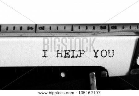 Typewriting on an old typewriter. Typing text: i help you