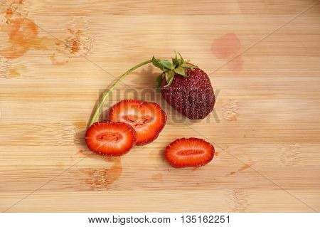 Lonely dark red strawberry on a chopping board