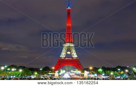paris; France-June 13 2016 : The Eiffel tower lit up in color of Spain's flag for soccer Europe championship 2016 in France. The Eiffel tower is on of the most visited monuments in the world.