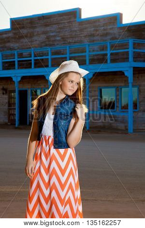 A teenage cowgirl wearing a long chevron pattern skirt and denim jacket with a western hat plays with her long back lit hair as she glances over her shoulder.