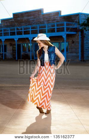 A teenage cowgirl looks down as she gives a little curtsy. She is wearing a western hat boots and a long modern skirt.