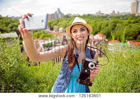 Here I am. Beautiful young woman is making selfie on a mobile phone. She is standing and holding a camera. Girl is laughing