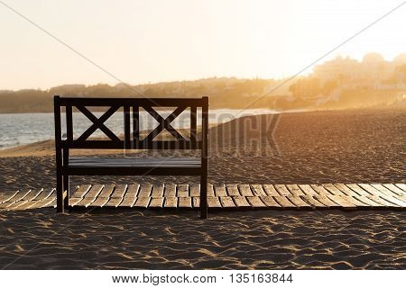 Bench on the beach at yellow sunset. Portugal Armacao de Pera.