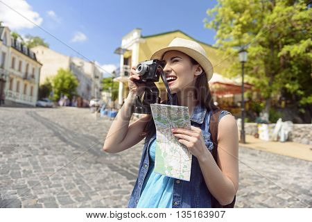 Joyful female tourist is taking photos of city. She is standing and laughing. Girl is carrying a guide map