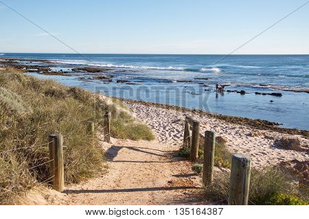 KALBARRI,WA,AUSTRALIA-APRIL 21,2016: Tourists wading in the Indian Ocean waters with dune path and clear skies in Kalbarri, Western Australia.