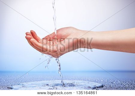 Water Falling In Woman's Hand On White And Blue