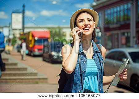 Cheerful young woman is making trip across city. She is talking on mobile phone and laughing. Girl is standing and holding guide map