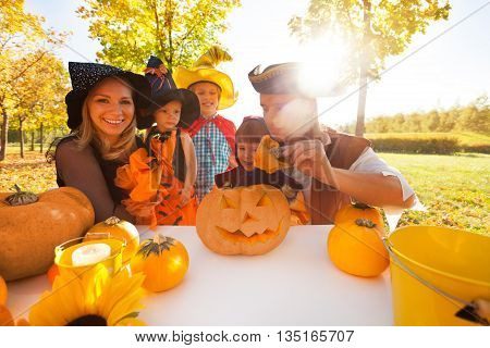 Family in Halloween costumes crafting Jack-O'-Lantern from pumpkin sitting at the table outside during beautiful sunny autumn day