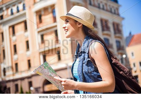 Joyful female tourist is walking across city. Girl holding a guide map and laughing