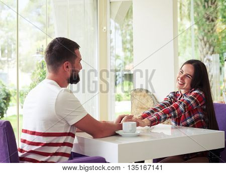 Young pretty woman is smiling shyly while she and her boyfriend are holding hands sitting on a bright cozy terrace with garden view