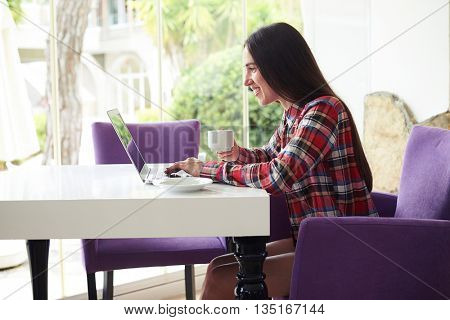 Sideview of young attractive woman in casual clothes sitting on terrace with broad garden view window typing on her laptop
