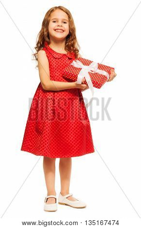 Little girl with curly hair stand with small red present and red dress isolated on white