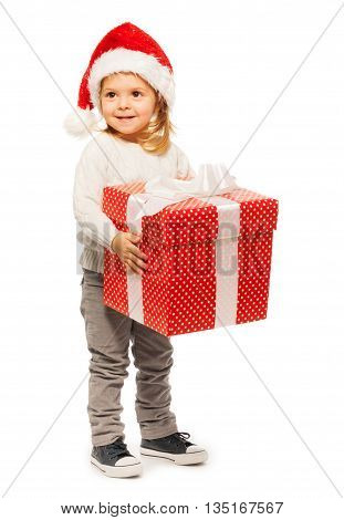 Small smiling 3 years old girl handling big polka dot red present adorned with white ribbon and bow dressed with Santa's hat