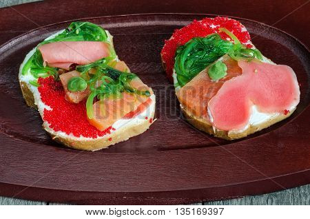 Two colourful sandwiches with seafood lay on a wooden tray