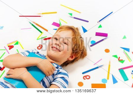 Close up picture of smiling five years old boy with book, having a rest among heap of stationery