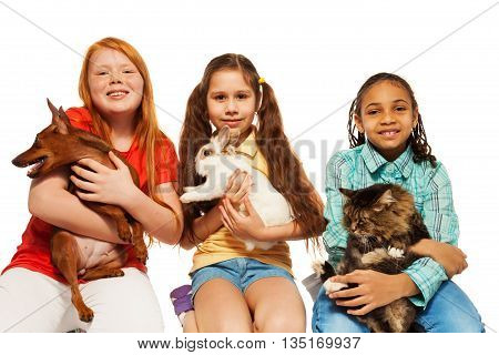 Diverse girls playing with their pets together, hugging cat, dog and rabbit isolated on white