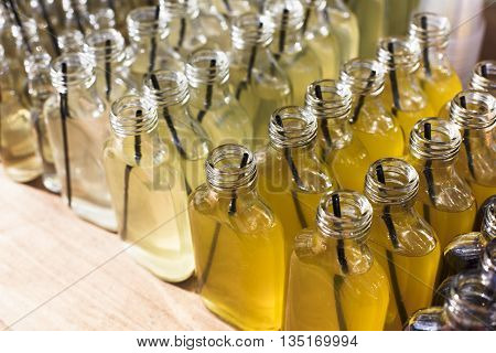 Alcohol cocktails, shots in glass bottles. Row of many alcohol tasty shots with straws in small bottles. Creative cocktails. Unusual alcohol in bar, many, plenty of drinks for party., catering, event
