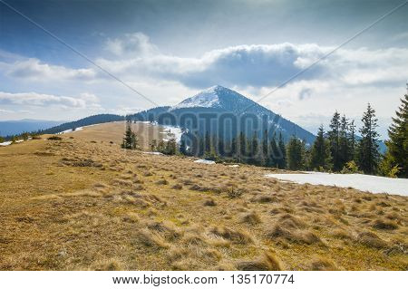 Mountain in windy sunny day with cloud overhead