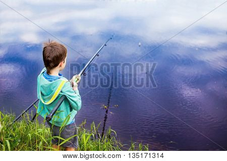 boy with a fishing rod standing by the water. young fisherman on a fishing trip. back view. copy space for your text
