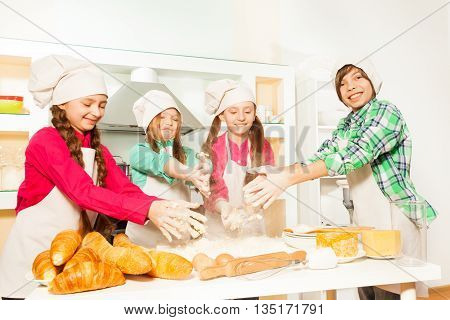 Four young cooks, boy and three girls in uniform, kneading flour and eggs for bakery dough in the kitchen