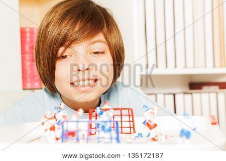 Close-up picture of smiling boy playing indoors ice hockey table board game