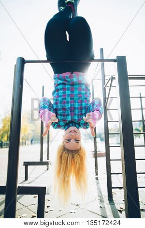 Young beautiful woman hanging upside down on horizontal bar at calisthenics park, looking at the camera giving thumbs up