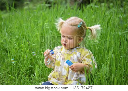 Beautiful Baby Girl Blowing Soap Bubbles In The Park
