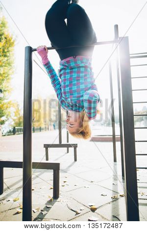 Young beautiful woman hanging upside down on horizontal bar at calisthenics park, looking off the camera and holding her hair