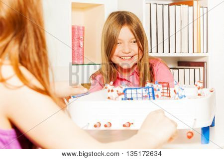 Happy girl playing table board hockey with her friend in the room
