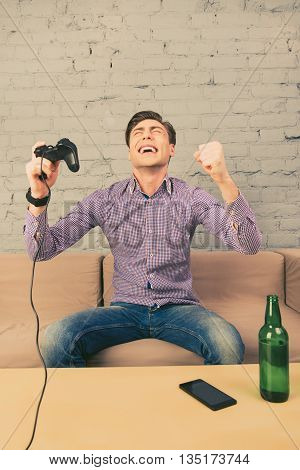 Excited Man Winning Video Game And Triumphing With Raised Hands