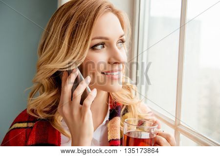 Portrait Of Beautiful Woman Basking With Plaid And Tea And Talking On Phone