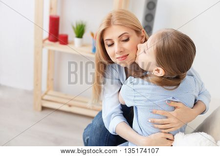 Hugging my perfect little angel. Sweet little girl hugging and kissing her beautiful young mom in cheek while sitting on sofa at home