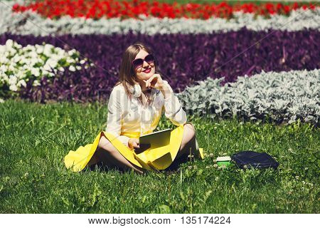 Student girl or young woman holds  tablet pc outdoors. Girl with earphones wears sunglasses sitting on the grass in the park. Music leisure. Having fun, rest, relax in park.
