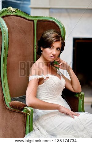Beauty bride in lace bridal gown indoors. Beautiful model girl in a white wedding dress. Female portrait of cute lady. Woman with hairstyle