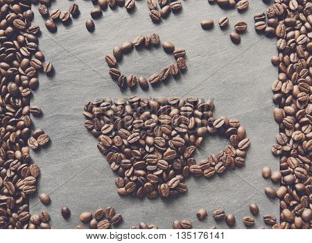 Cup from coffee beans. Heap of roasted coffee bean on grey stone surface texture. Coffee shop or cafe background. Natural stone and cup from beans. Soft color toning, top view