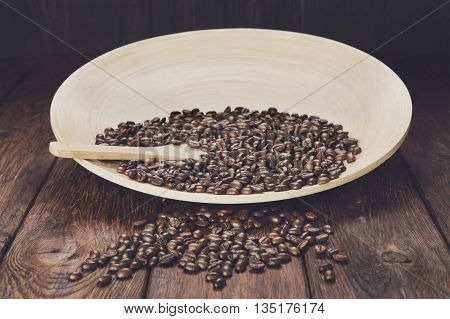 Coffee beans in bamboo plate or bowl with wooden spoon on rustic brown wood table. Coffee crop scattered on table, soft toning. Plenty of robusta beans in plate. Seeds of coffee at wooden background.