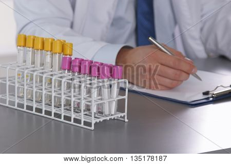 Male Doctor Write On The Desk With Test Tube