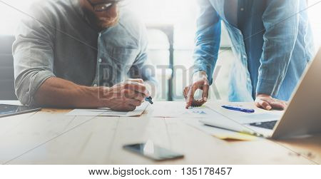 Coworkers team brainstorming process in modern office.Project manager wearing glasses, man makes notes marker.Young business crew working with startup studio.Laptop wood table.Blurred, film effect.Wide
