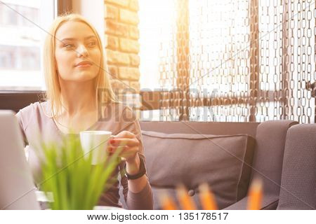 Pensive young businesswoman is drinking coffee with enjoyment. She is looking forward and dreaming. Lady is sitting at table near laptop in cafe