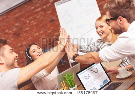 Success in teamwork. Happy young colleagues are giving high five. They are sitting at desk and laughing