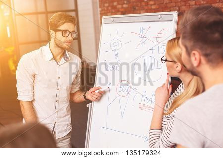 Smart young man is sharing his ideas with colleagues. He is standing and pointing at board with seriousness. Man and woman are listening to him attentively