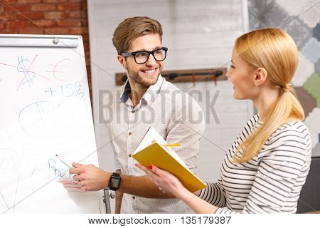 Attractive young man is explaining his ideas to colleague. He is standing and pointing at board with aspiration. Woman is making notes and smiling