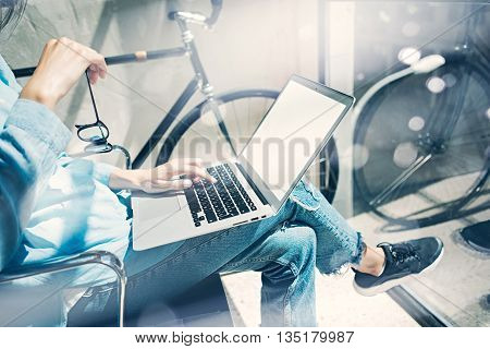 Work process modern design Studio Loft.Creative manager working coworkers office new freelance business startup.Using Laptop knees, holding glasses hand.Reflection.Horizontal mockup.Film effect.Blurred