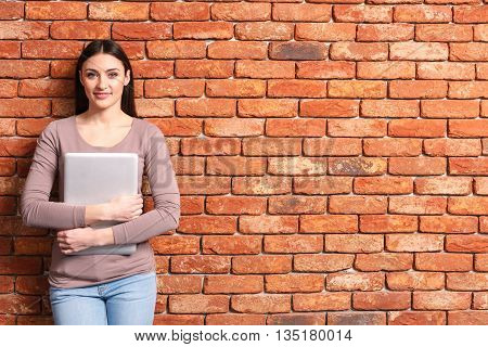 Smart young girl is holding and hugging her laptop. She is looking forward and smiling. Student is standing and leaning on wall. Copy space in right side