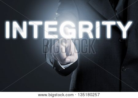 Businessman pointing at the word 'integrity' - business moral or ethics concept