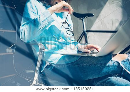 Work process modern Studio Loft.Creative Art director working coworkers office with new freelance business startup.Using Laptop on knees, holding glasses hand.Horizontal.Film effect.Blurred background